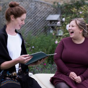 A woman and a therapist talking in a garden.